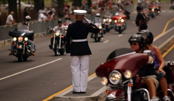 Marine Staff Sgt. Tim Chambers from San Diego, California, stands at attention for hours to salute the tens of thousands of motorcyclists who participate in the annual Rolling Thunder Ride for Freedom in Washington. Photo by The Washington Times.