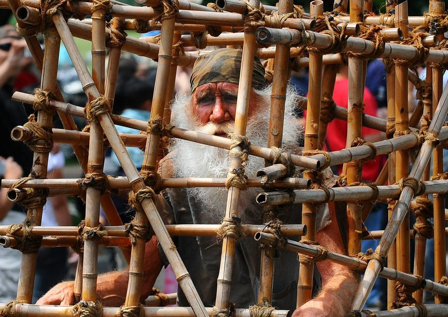 A man role-plays the part of a POW in a cage as he is pulled by a motorcycle, during the Rolling Thunder XXII Ride for Freedom along Constitution Avenue in Washington, D.C., Sunday, May 24, 2009.  (Rod Lamkey Jr. / The Washington Times)