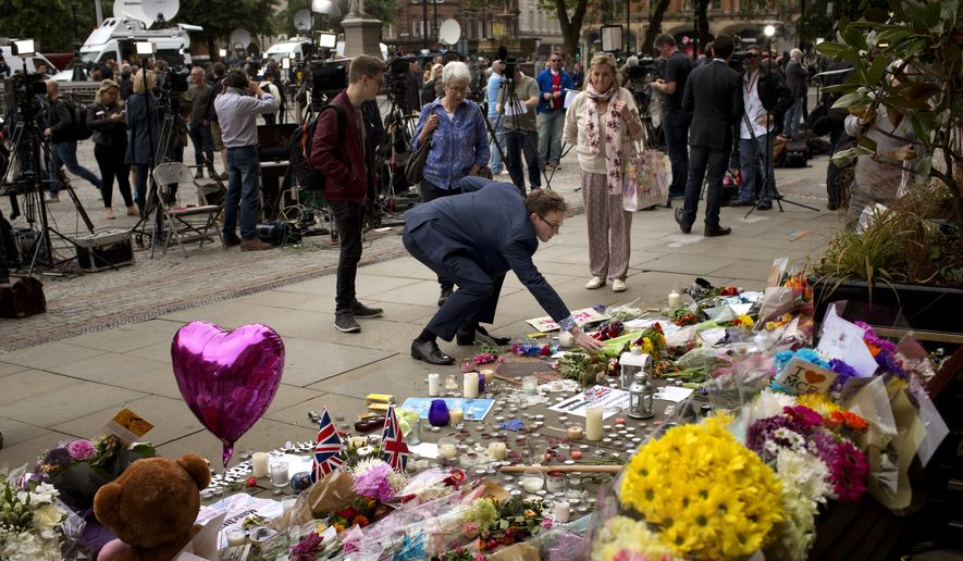 A man places flowers in Albert Square in Manchester, Britain, Wednesday, May 24, 2017, after the suicide attack at an Ariana Grande concert that left more than 20 people dead and many more injured, as it ended on Monday night at the Manchester Arena. (AP Photo/Emilio Morenatti)