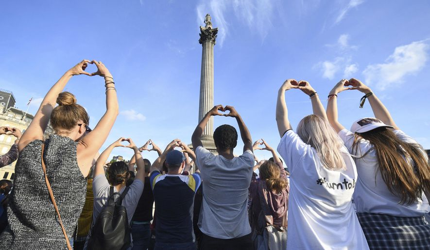 People gesture as they attend a vigil in Trafalgar Square, London Tuesday May 23, 2017 for the victims of the attack which killed over 20 people as fans left a pop concert by Ariana Grande in Manchester on Monday night. (Victoria Jones/PA via AP)