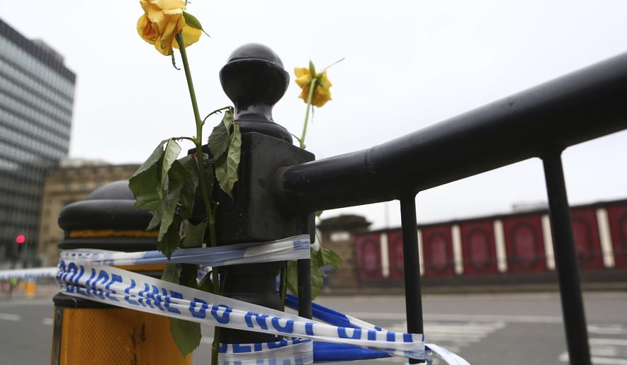 Flowers are attached to a railing close to Victoria Railway Station in Manchester, Britain, Wednesday, May 24, 2017, after Monday's suicide attack at an Ariana Grande concert. Britons will find armed troops at vital locations Wednesday after the official threat level was raised to its highest point. (AP Photo/Dave Thompson)