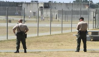 FILE - In this Aug. 17, 2011 file photo, correctional officers keep watch on inmates in the recreation yard at Pelican Bay State Prison near Crescent City, Calif. Officials say several California prison guards and inmates were taken to hospitals after a fight between two inmates quickly raged out of control Wednesday, May 24, 2017. (AP Photo/Rich Pedroncelli, File)