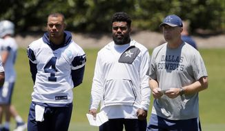 Dallas Cowboys' Dak Prescott (4), Ezekiel Elliott, center, and offensive coordinator Scott Linehan, right, watch the team run through drills during NFL football organized team activities at the team's training facility, Wednesday, May 24, 2017, in Frisco, Texas. (AP Photo/Tony Gutierrez)