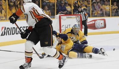 Anaheim Ducks center Ryan Getzlaf (15) shoots the puck past Nashville Predators left wing Viktor Arvidsson (38), of Sweden, and Nashville Predators goalie Pekka Rinne (35), of Finland, during the third period in Game 6 of the Western Conference final in the NHL hockey Stanley Cup playoffs Monday, May 22, 2017, in Nashville, Tenn. (AP Photo/Mark Humphrey)
