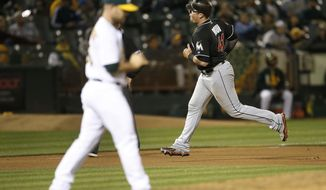 Miami Marlins' Justin Bour, right, rounds the bases after hitting a solo home run as Oakland Athletics relief pitcher Daniel Coulombe, left, walks back to the mound during the seventh inning of a baseball game on Tuesday, May 23, 2017, in Oakland, Calif. (AP Photo/Tony Avelar)
