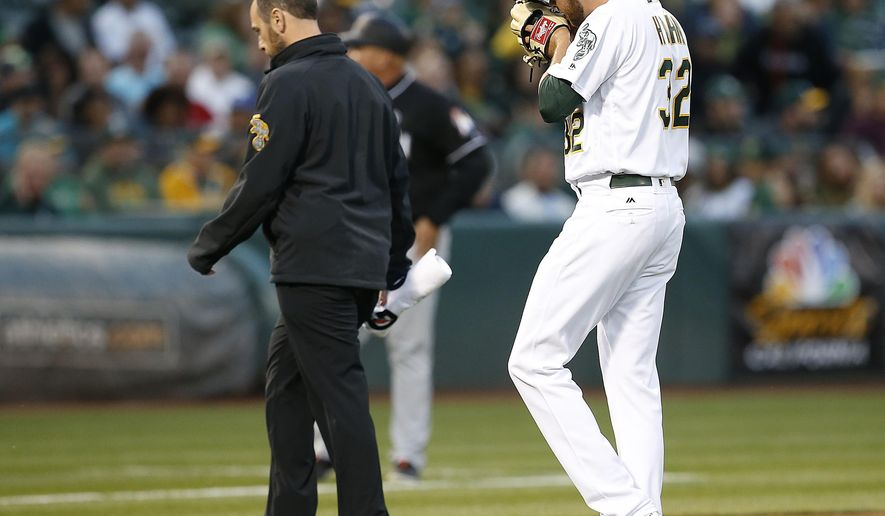 Oakland Athletics pitcher Jesse Hahn (32) walks off the field with the team trainer during the third inning against the Miami Marlins in a baseball game on Tuesday, May 23, 2017 in Oakland, Calif. (AP Photo/Tony Avelar)