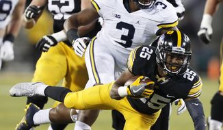 FILE  - In this Saturday, Nov. 12, 2016 file photo, Iowa running back Akrum Wadley (25) tries to get away from Michigan defender Rashan Gary (3) during the second half of an NCAA college football game in Iowa City, Iowa. Gary was a contributor to last season's excellent Michigan defense, making 27 tackles and five for loss. (AP Photo/Charlie Neibergall, File)