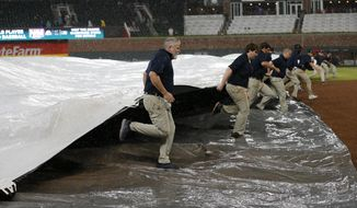 Members of Atlanta Braves grounds crew race to cover the infield during a rain delay in the seventh inning of a baseball game against the Pittsburgh Pirates, Tuesday, May 23, 2017, in Atlanta. (AP Photo/John Bazemore)