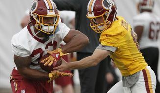 Washington Redskins running back Samaje Perine (32) takes a handoff from quarterback Kirk Cousins (8) during practice at the team's NFL football training facility at Redskins Park, Wednesday, May 24, 2017 in Ashburn, Va. (AP Photo/Alex Brandon)