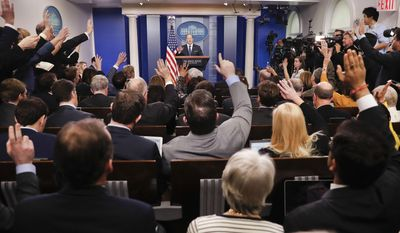 In this Feb. 22, 2017, file photo, reporters raise their hands as White House press secretary Sean Spicer takes questions during the daily briefing in the Brady Press Briefing Room of the White House in Washington. On June 30, 2017, the White House Correspondent Association awarded Newsmax and One America News Network, two conservative cable outlets, new assigned seats in the briefing room, Politico reported.(AP Photo/Pablo Martinez Monsivais, File)