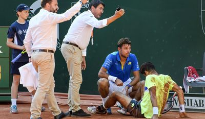 Switzerland's Stan Wawrinka, centre right, attends to Brazil's Rogerio Dutra Silva, during their second round match of the Geneva Open tennis tournament in Geneva, Switzerland, Wednesday, May 24, 2017.  Dutra Silva retired from the match due to an injury. (Martial Trezzini/Keystone via AP)