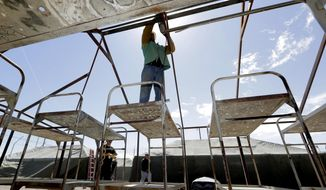 Maricopa County Sheriff personnel break down a tent in the Tent City Jail, Wednesday, May 24, 2017, in Phoenix. Crews have started to dismantle some of the tents in the controversial outdoor jail complex in Phoenix that's in the process of being closed by the metro area's new sheriff. (AP Photo/Matt York)
