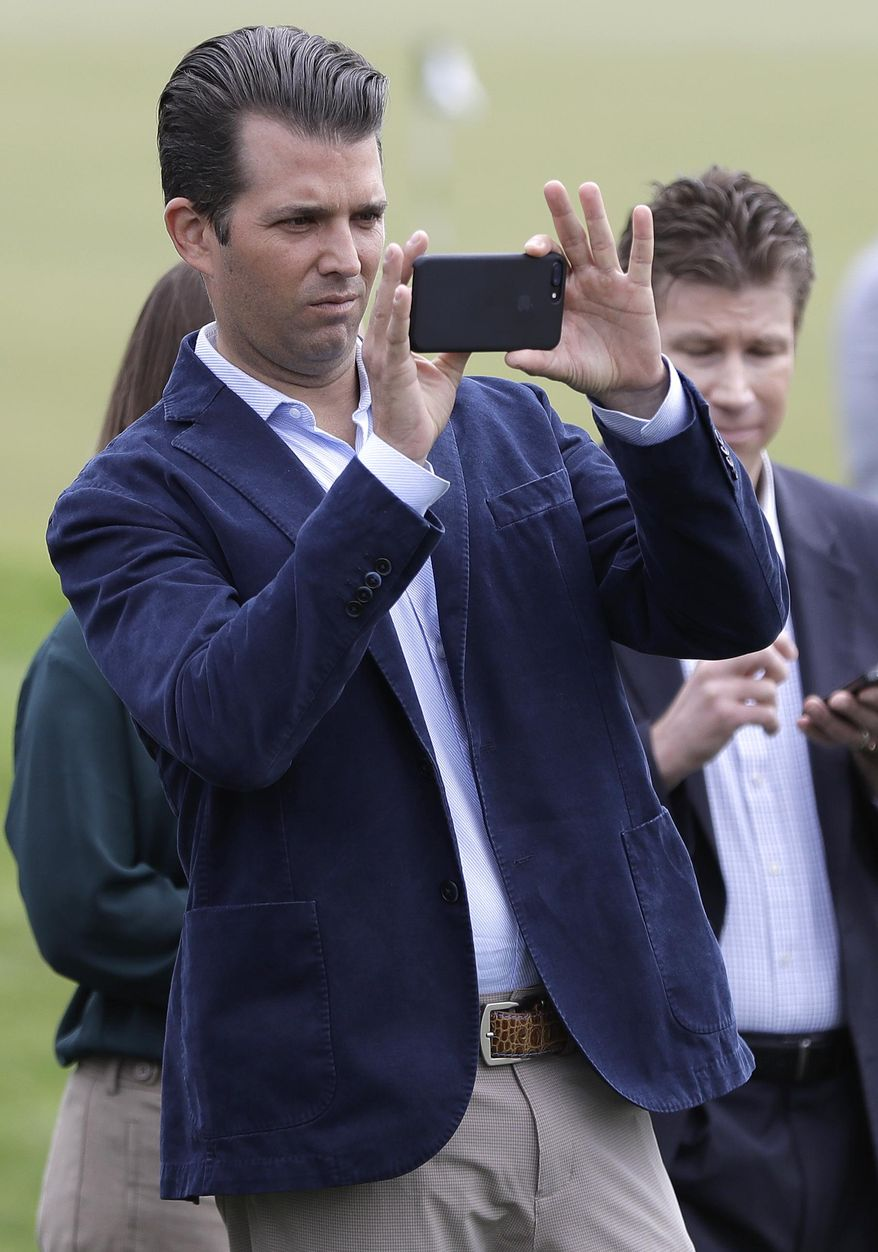 Donald Trump Jr. uses a smartphone to take images of a youth golf clinic hosted by professional golfers Brittany Lang, Cristie Kerr and Lydia Ko, of New Zealand, during an event previewing the U.S. Women's Open Championship golf tournament at Trump National Golf Club, Wednesday, May 24, 2017, in Bedminster, N.J. (AP Photo/Julio Cortez)