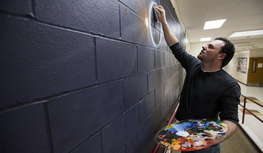 In this May 17, 2017 photo, local artist Jason Sanchez paints a galaxy mural in the front hallway of Ramsey Magnet School of Science in Coeur d'Alene, Idaho. Sanchez, a disabled Army veteran, has been spending several hours each weeknight since mid-April to complete the solar system mural at no cost to his childhood school. He plans to have it done in early June. (Loren Benoit/Coeur D'Alene Press via AP)
