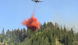 In this May 23, 2017 photo provided by Chelan County Fire District 3, an air tanker drops fire retardant on forest land as a wildfire burns near Leavenworth, Wash. The wildfire that started at an old log-storage site has prompted evacuation orders for homes and cabins at a popular Washington state hiking and skiing destination, officials said Wednesday. (Ben Torkelson/Chelan County Fire District 3 via AP)