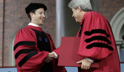 Facebook CEO and Harvard dropout Mark Zuckerberg, left, is presented with an honorary Doctor of Laws degree by Vice President and Secretary of Harvard University Marc Goodheart, right, during Harvard University commencement exercises, Thursday, May 25, 2017, in Cambridge, Mass. (AP Photo/Steven Senne)