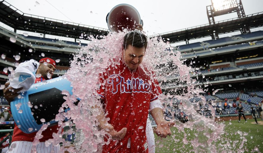 Philadelphia Phillies' Tommy Joseph, center, is doused by Andres Blanco, left, and Cameron Rupp after Joseph hit the game winning RBI-single in the 11th inning of a baseball game against the Colorado Rockies, Thursday, May 25, 2017, in Philadelphia. Philadelphia won 2-1. (AP Photo/Matt Slocum)