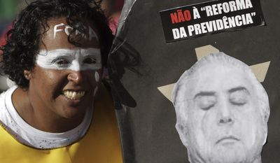 "A woman, with the Portuguese word for ""Out"" painted on her forehead, poses next to a montage featuring Brazil's President Michel Temer and the message ""No to welfare reform"", during an anti-government protest in Brasilia, Brazil, Wednesday, May 24, 2017. Temer's attempt to win back confidence and stay in power was undermined Tuesday as one aide was arrested in a fraud scheme, another aide turned over to police a bag full of cash and shouts of ""down with Temer"" led a Senate commission to suspend work on a package of the president's labor reforms. (AP Photo/Eraldo Peres)"