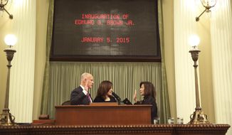 File - In this Jan. 5, 2015 file photo, California Gov. Jerry Brown, left, takes the oath of office from Chief Justice of the California Supreme Court Tani Cantil-Sakauye, right, as his wife, Anne Gust Brown, center, looks on during his inauguration at the state Capitol in Sacramento, Calif. Cantil-Sakauye says after six years she still hasn't quite figured out Gov. Jerry Brown. Cantil-Sakauye said Thursday, May 25, 2017, that she didn't know what to expect the first time they met after she became head of the state's high court. (AP Photo/Rich Pedroncelli, File)