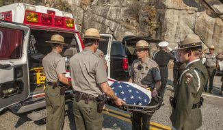 FILE - In this Oct. 8, 2014, file photo, Yosemite National Park Rangers transfer the body of a Cal Fire pilot who was killed in an airplane crash in Yosemite National Park, Calif. An investigation into the 2014 fatal crash found that the pilot was warned to avoid a hazardous tree to the right of his flight path before a wing struck trees to the left, according to a National Transportation Safety Board report released Wednesday, May 24, 2017. (AP Photo/Al Golub, File)