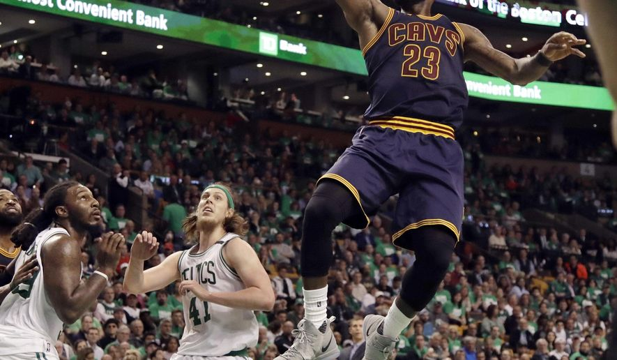 Cleveland Cavaliers forward LeBron James (23) soars to the basket over Boston Celtics forward Jae Crowder, left, and center Kelly Olynyk (41) during the second half of Game 5 of the NBA basketball Eastern Conference finals, on Thursday, May 25, 2017, in Boston. (AP Photo/Elise Amendola)