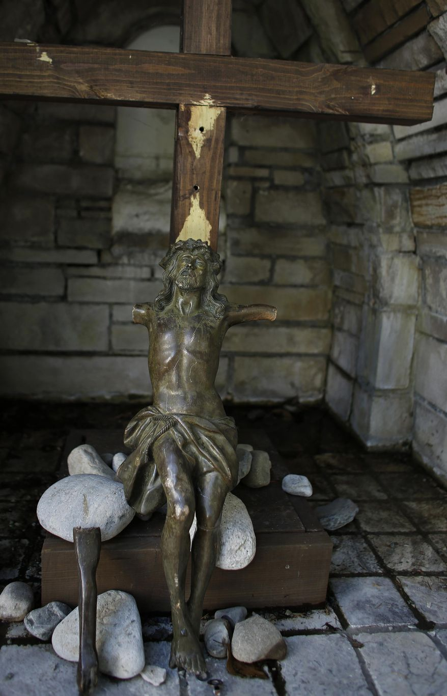 Though badly damaged, part of a statue of Jesus stolen from a crucifix in a park outside Norfolk's Holy Trinity Catholic Church has been returned as seen Thursday, May 25, 2017 in Norfolk, Va. (Stephen M. Katz/The Virginian-Pilot via AP)