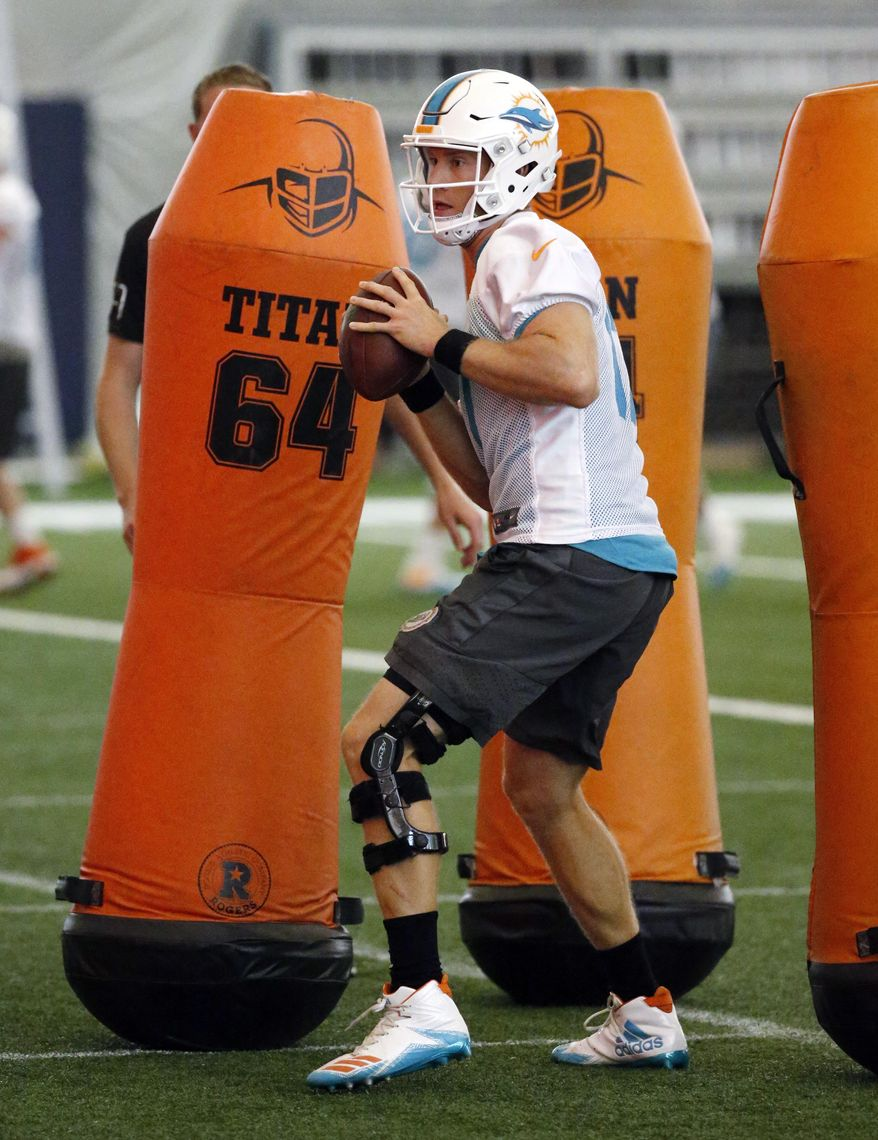 Miami Dolphins quarterback Ryan Tannehill runs through drills during NFL football organized team activities, Thursday, May 25, 2017, at the Dolphins training facility in Davie, Fla. (AP Photo/Wilfredo Lee)