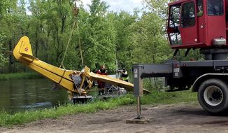 Divers with a towing service pull a plane that crashed into the Red Cedar River, about 3 miles south of Chetek, Wis. on Wednesday, May 24, 2017. Sheriff's officials say one teenager died and another was critically injured in the crash. (Pam Powers/The Eau Claire Leader-Telegram via AP)