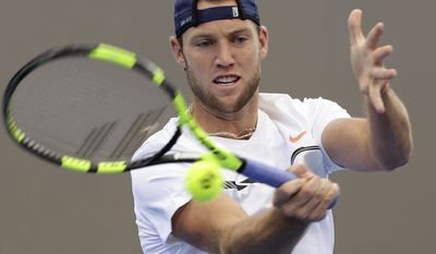 FILE - In this April 7, 2017, file photo, Jack Sock, of the United States, plays a shot in his match against Jordan Thompson, of Australia, at the Davis Cup World Group quarterfinals in Brisbane, Australia. Sock will be competing in the French Open tennis tournament. (AP Photo/Tertius Pickard, File)