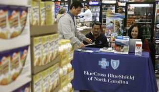 FILE - In this Saturday, Nov. 22, 2014, file photo, Blue Bridge Benefits LLC agent Patricia Sarabia, right, and Adolfo Briceno, left, with Spanish Speaking LLC, help a potential customer with Blue Cross Blue Shield at a kiosk promoting health insurance under the federal Affordable Care Act, at Compare Foods in Winston-Salem, N.C. People shopping for insurance through the Affordable Care Act in yet more regions will be facing higher prices and fewer choices in the coming year as insurance companies lay out their early plans for 2018. Blue Cross and Blue Shield of North Carolina said Thursday, May 25, 2017, it wants a 23 percent price hike in 2018 because it doesn't expect crucial payments from the federal government to continue. (AP Photo/Gerry Broome, File)