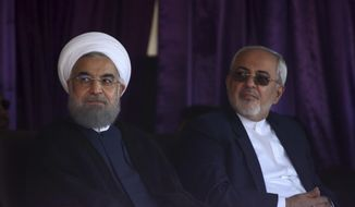 In this picture taken on Sunday, May 14, 2017, Iranian President Hassan Rouhani, left, sits during a presidential election campaign as he is accompanied by his Foreign Minister Mohammad Javad Zarif in the city of Isfahan, Iran. (AP Photo/Vahid Salemi)
