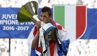 Juventus' Mario Mandzukic kisses the trophy as  Juventus players celebrate winning an unprecedented sixth consecutive Italian title, at the end of the Serie A soccer match between Juventus and Crotone at the Juventus stadium, in Turin, Italy, Sunday, May 21, 2017. (AP Photo/Antonio Calanni)