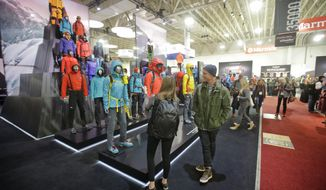 FILE - In this Jan. 11, 2017, file photo, people attend the Outdoor Retailer show at the Salt Palace Convention Center in Salt Lake City. Two major outdoor recreation trade shows are merging for one big expo to be held in Denver. Emerald Expositions, which produces the Outdoor Retailer trade show that's leaving Salt Lake City after two decades over political differences, announced Wednesday, May 24, 2017, it has acquired the SnowSports Industries America Snow Show that is held each winter in Denver. (AP Photo/Rick Bowmer, File)