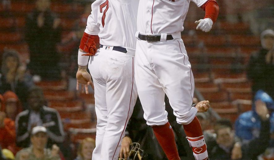 Boston Red Sox's Deven Marrero, right, celebrates with teammate Christian Vazquez after knocking him in on a two-run home run during the eighth inning of a baseball game against the Texas Rangers at Fenway Park in Boston, Thursday, May 25, 2017. (AP Photo/Mary Schwalm)