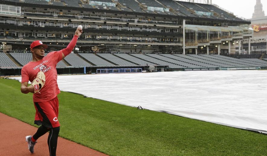 Cincinnati Reds relief pitcher Wandy Peralta warms up in the rain after an interleague baseball game between the Cincinnati Reds and the Cleveland Indians was postponed, Thursday, May 25, 2017, in Cleveland. (AP Photo/Tony Dejak)