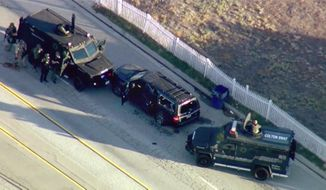 FILE - In this Dec. 2, 2015, file image, taken from video, armored vehicles surround an SUV following a shootout in San Bernardino, Calif. Authorities have released a detailed report that includes the accounts of more than two dozen law enforcement officers involved in a shootout with a husband and wife who killed 14 people and wounded 22 others in the San Bernardino terror attack. San Bernardino County prosecutors released the report Thursday, May 25, 2017. (KTTV via AP, File)