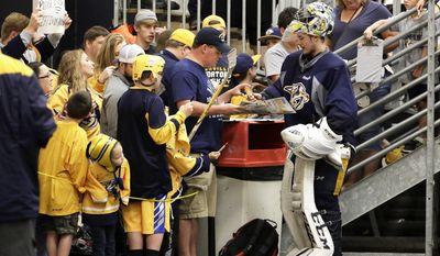 Nashville Predators goalie Juuse Saros, of Finland, signs autographs for fans after practice at the team's NHL hockey facility Thursday, May 25, 2017, in Nashville, Tenn. (AP Photo/Mark Humphrey)