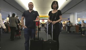 In this Friday, May 12, 2017, photo, Associated Press journalists Scott Mayerowitz and Candice Choi pose at New York's LaGuardia Airport while traveling together to compare the experiences of elite travelers with status and those without. (AP Photo/Scott Mayerowitz)
