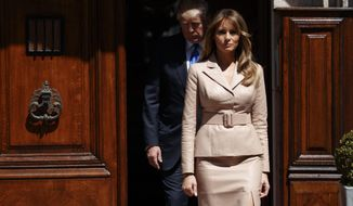 First lady Melania Trump and President Donald Trump arrive to greet French President Emmanuel Macron at the U.S. Embassy, Thursday, May 25, 2017, in Brussels. (AP Photo/Evan Vucci)