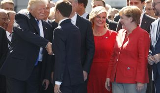 German Chancellor Angela Merkel watches at right as President Donald Trump shakes hands with French President Emmanuel Macron during a ceremony to unveil artifacts from the World Trade Center and Berlin Wall for the new NATO headquarters, Thursday, May 25, 2017, in Brussels. (AP Photo/Evan Vucci)