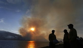FILE - In this Aug. 26, 2016 file photo, firefighters just in from Pennsylvania get briefed on a wildfire as it burns off the shore of Jackson Lake in Grand Teton National Park, Wyo. State forester Bill Crapser says most of Wyoming is predicted to have slightly below average to average large wildfires this year. Crapser says there could be a lot of wildfires started by lightning but most are not expected to grow into large fires. The predictions come from the Rocky Mountain Area Coordination Center in Denver. (AP Photo/Brennan Linsley, File)