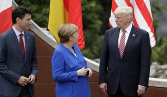 German Chancellor Angela Merkel, center, speaks with U.S. President Donald Trump, right, as Canadian Prime Minister Justin Trudeau stands left, during a group photo at the G-7 Summit in the Ancient Theatre of Taormina (3rd century BC) in the Sicilian citadel of Taormina, Italy, Friday, May 26, 2017. Leaders of the G-7 meet Friday and Saturday, including newcomers Emmanuel Macron of France and Theresa May of Britain in an effort to forge a new dynamic after a year of global political turmoil amid a rise in nationalism. (AP Photo/Andrew Medichini)