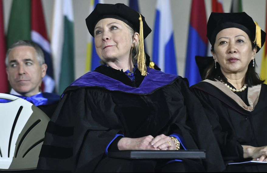 Former Secretary of State Hillary Clinton reacts to her introduction while sitting with faculty members before she delivered the commencement address at Wellesley College, Friday, May 26, 2017, in Wellesley, Mass. Clinton graduated from the school in 1969. (AP Photo/Josh Reynolds)