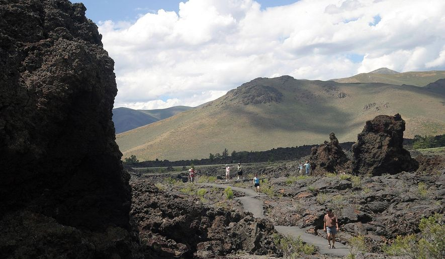 FILE - In this July 2012 file photo, people hike the North Crater Flow Trail at Craters of the Moon National Monument, Idaho. Federal officials have released a cattle grazing plan for central Idaho's Craters of the Moon National Monument and Preserve that immediately came under fire from an environmental group. The U.S. Bureau of Land Management's Final Environmental Impact Statement released Friday, May 26, 2017, allows cattle grazing on nearly all of the roughly 275,000 acres it administers in the monument. (Tetona Dunlap/The Times-News via AP, File)