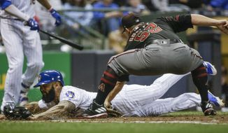 Milwaukee Brewers' Eric Thames, bottom, is tagged out at home by Arizona Diamondbacks' Zack Godley on a runner's fielder's choice during the sixth inning of a baseball game Friday, May 26, 2017, in Milwaukee. (AP Photo/Tom Lynn)