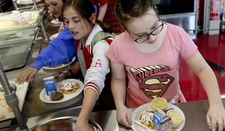 In a Friday, May 19, 2017 photo, Cara Hjorth, 6th-grader, right, inputs her student number to pay for lunch at Mount Jordan Middle School in Sandy, Utah. Canyons School District administrators are proposing that the school board adopt a policy that takes a kinder, gentler approach to school nutrition service to children whose accounts are in arrears. (Laura Seitz/The Deseret News via AP)