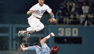 FILE - In this Oct. 6, 1984 file photo, Philadelphia Phillies' Mike Schmidt tries to take out Los Angeles Dodgers' Steve Sax at second to break up an eighth inning double-play to no avail during their second National League playoff game in Los Angeles. Steve Sax won two World Series rings, was a five-time All-Star and got nearly 2,000 hits in the big leagues. Yet to many fans, it's those half-dozen lines he uttered to a bunch of yellow cartoon characters a long time ago that really made him famous. (AP Photo/File)