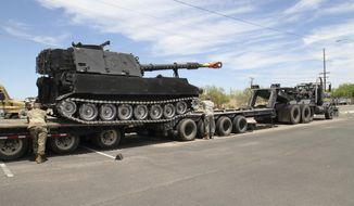 In this Thursday, May 25, 2017, photo provided by the Maricopa County Sheriff's Office, MCSO shows the Department of Defense taking possession of a 1960's era self-propelled howitzer from the Maricopa County Sheriff's Department in Phoenix. The Arizona Army National Guard transported the M-109 via flatbed truck to its facilities in Phoenix. (Maricopa County Sheriff's Office via AP)