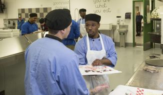 """In this May 23, 2017 photo, inmate Jonathan Scott, right, works in the kitchen at the Cook County Jail in Chicago. Inmates in the jail's medium-security Division 11 are now allowed to order pizzas made by inmates like Scott, who is participating in the jail's """"Recipe for Change"""" program while he waits for trial after his 2015 arrest on an armed robbery charge. in Chicago. (AP Photo/Teresa Crawford)"""