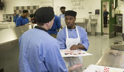 "In this May 23, 2017 photo, inmate Jonathan Scott, right, works in the kitchen at the Cook County Jail in Chicago. Inmates in the jail's medium-security Division 11 are now allowed to order pizzas made by inmates like Scott, who is participating in the jail's ""Recipe for Change"" program while he waits for trial after his 2015 arrest on an armed robbery charge. in Chicago. (AP Photo/Teresa Crawford)"